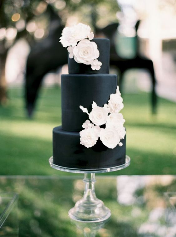 a matte black wedding cake with white sugar flowers is a stylsh and timeless idea that works