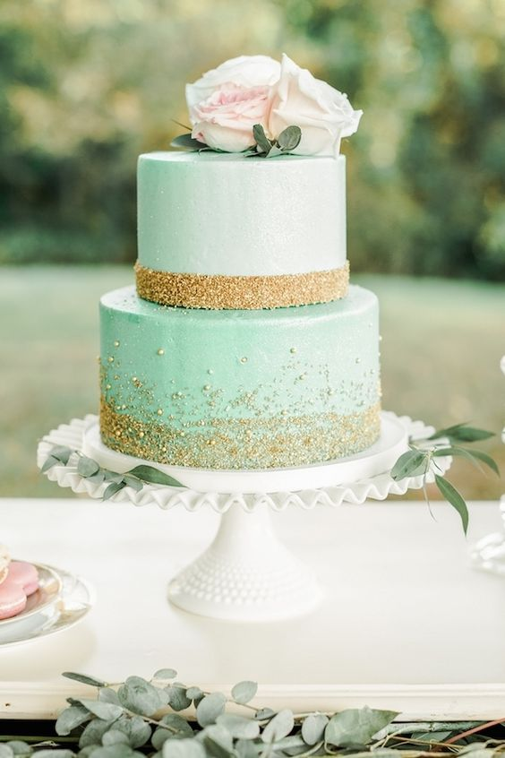 a mint-colored wedding cake with gold glitter, blush and white roses is very glam and elegant