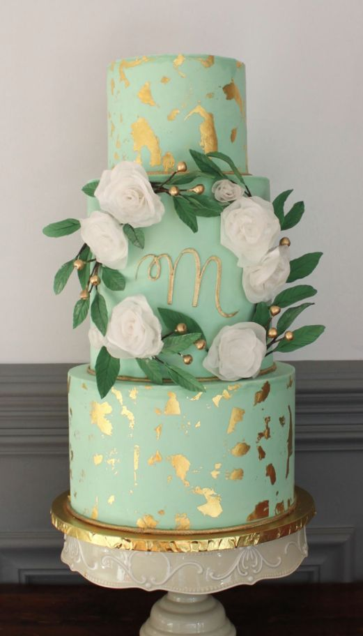 a mint wedding cake with gold leaf, white blooms and berries for decorating will match a spring or summer wedding