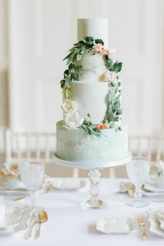 a mint wedding cake with plain and textural tiers, with sugar blooms and leaves