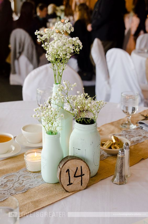 a mint wedding centerpiece composed of jars and bottles, baby's breath and candles