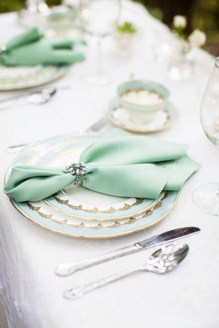 a mint, white and gold plates and a mint napkin with a brooch napkin ring for a refined tablescape