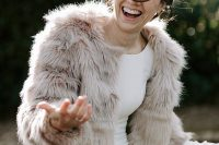 a modern winter bridal look with a plain fitting wedding dress and a neutral faux fur coat is cool and fresh