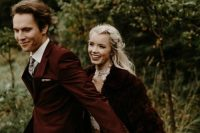 a neutral wedding dress with a high neckline, a burgundy faux fur jacket and an embellished headpiece for a Christmas wedding
