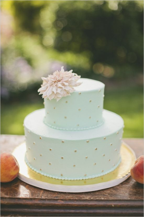 a pretty mint wedding cake with gold dots, with a pink bloom on top looks romantic