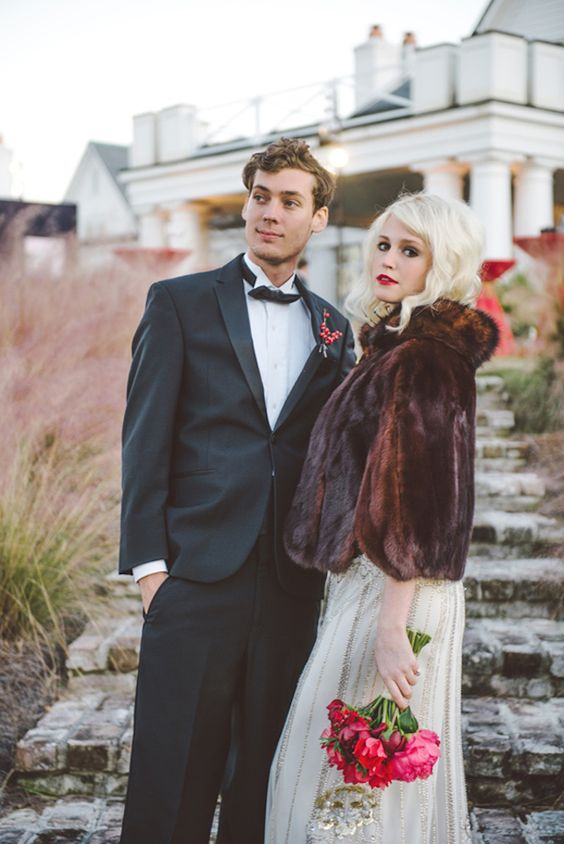 a refined embellished wedding dress paired with a dark faux fur cropped jacket with a collar and short sleeves for a contrasting look