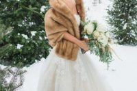 a refined lace strapless wedding ballgown with a beige faux fur stole are a great combo for a sophisticated winter bride