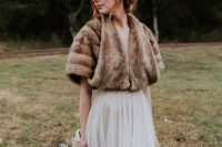 a romantic A-line wedding dress with a semi sheer skirt, a brown faux fur cover up and a greenery crown for a fall bride