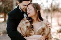 a romantic and refined winter bridal look with a plain wedding ballgown and a beige faux fur cover up plus statement earrings