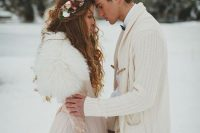 a romantic winter bridal look with a neutral A-line wedding dress of lace and a white faux fur cover up plus a floral crown