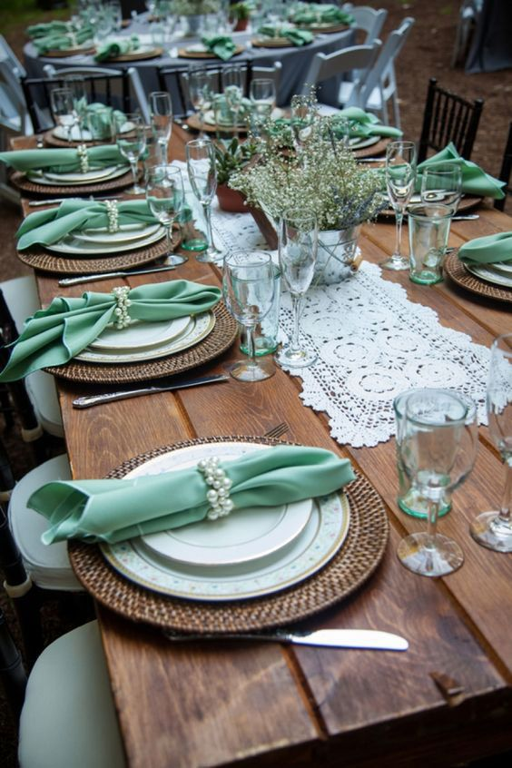 a rustic wedding tablescape with an uncovered table, a doily table runner, woven chargers and mint napkins and glasses