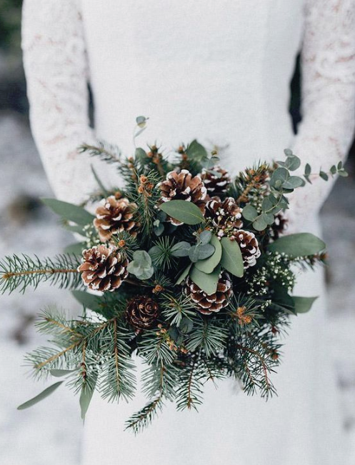 a simple and cozy winter wedding bouquet of evergreens, eucalyptus and snowy pinecones