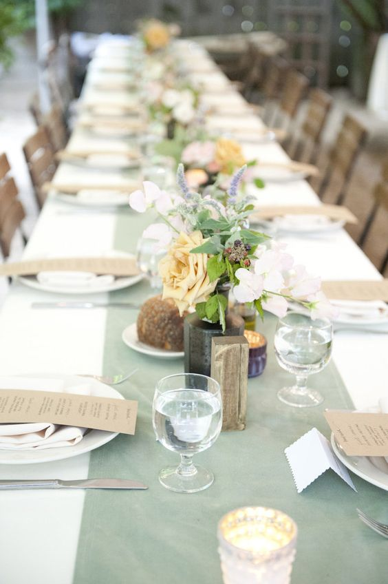 a simple and cute wedding tablescape with a mint table runner, neutral linens and pastel and white blooms