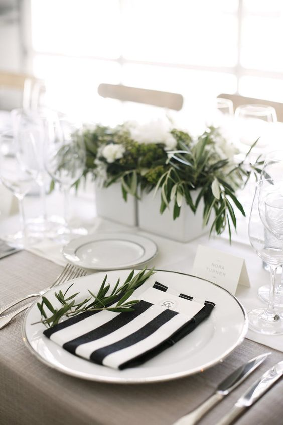 a simple modern tablescape with striped black and white napkins, much greenery and a neutral tablecloth