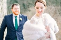 a sophisticated winter bridal look with a lace and plain fitting wedding dress and a white faux fur cover up is all chic