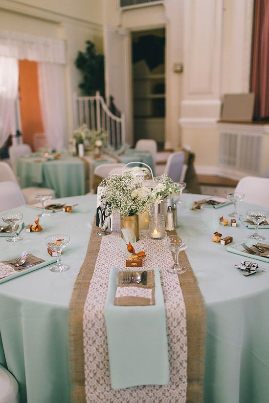 a spring wedding table with a burlap and lace table runner, mint napkins, white blooms and greenery centerpiece and candles