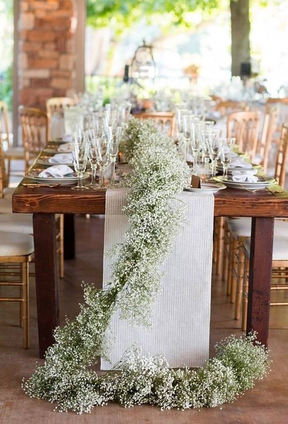 a striped fabric table runner and a baby's breath one combined for a refined rustic touch