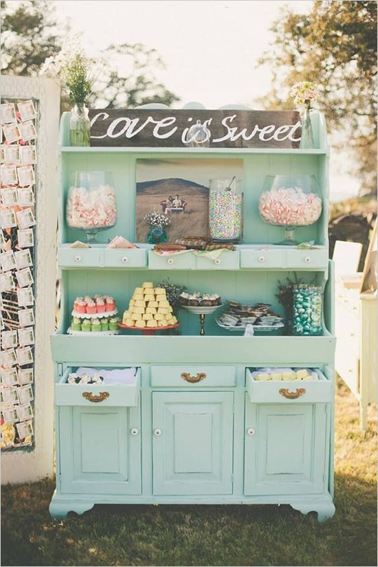 a wedding sweets bar of an oversized mint-colored buffet and lots of tasty sweets