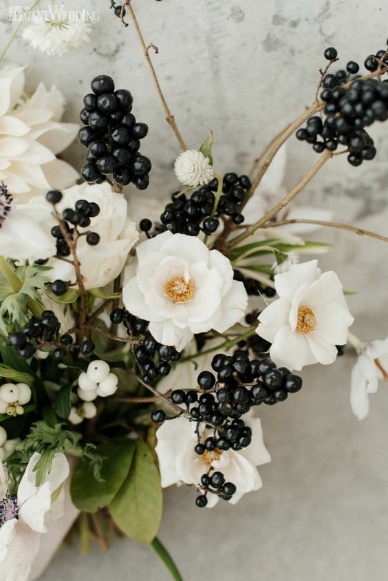 a white bloom wedding bouquet with black berries and touches of greenery is a chic casual idea