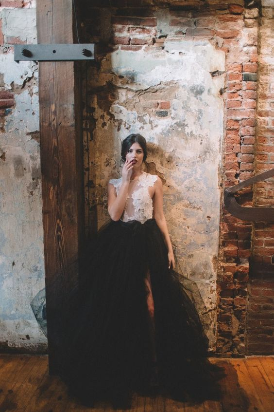 a white lace sleeveless top and a black tulle skirt with a front slit for a sexy modern bridal look