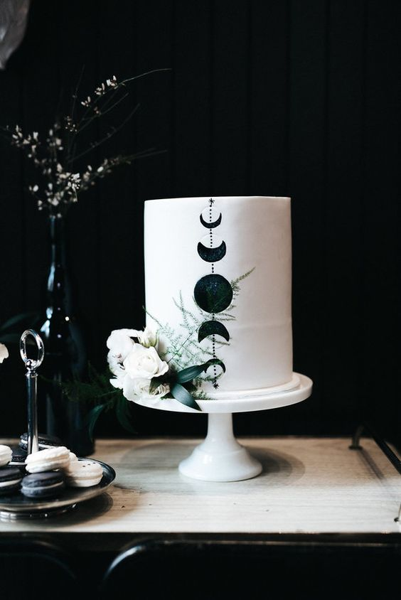 a white wedding cake decorated with black moon phases and white blooms and greenery is ideal for a celestial wedding