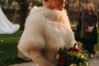 a winter wonderland bridal look with a lace A-line wedding dress and a faux fur cover up on top plus pearls