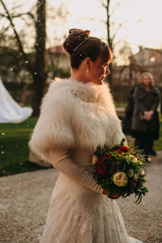 a winter wonderland bridal look with a lace A line wedding dress and a faux fur cover up on top plus pearls