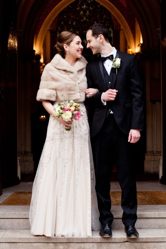 an art deco bridal outfit with an embellished A-line wedding dress with a neutral faux fur cropped jacket with short sleeves