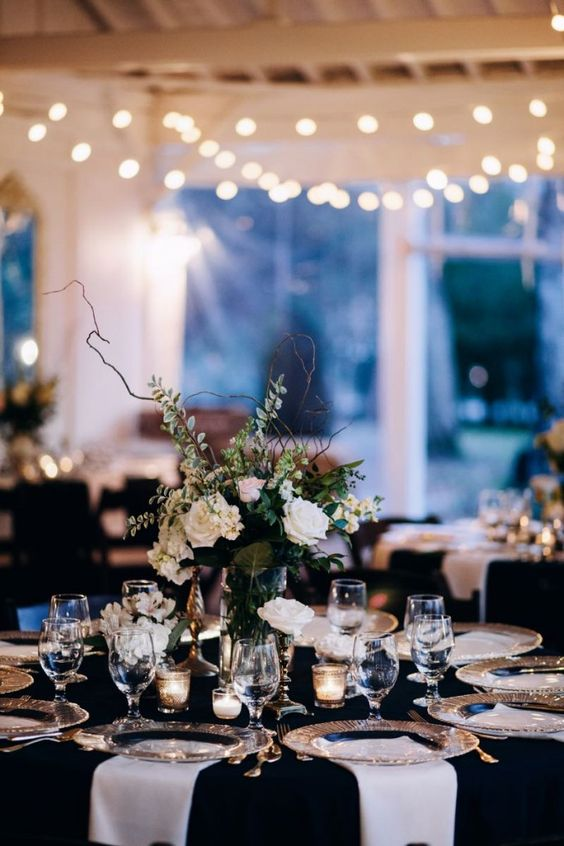 an elegant black and white table setting with a lush floral centerpiece, gold cutlery and candles