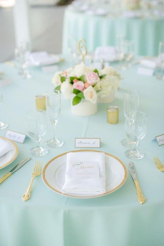 an elegant wedding table with a mint tablecloth, gold touches and a neutral and pink floral centerpiece is chic