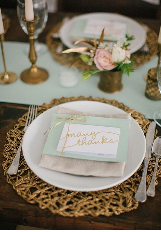 an elegant wedding tablescape with a mint table runner and a card plus touches of gold and brass