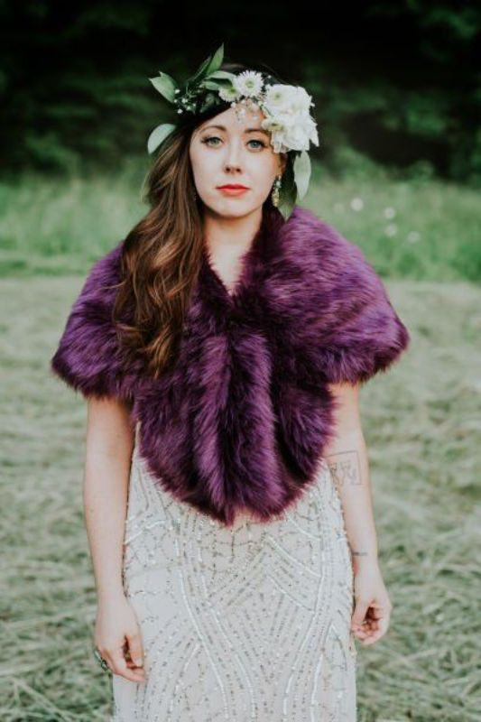 an embellished fitting wedding dress with a purple faux fur cover up and a white floral crown is a chic idea