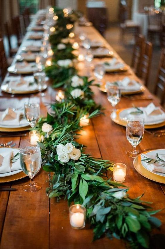 an uncovered table with a long greenery and white bloom garland plus candles that create a cool rustic feel