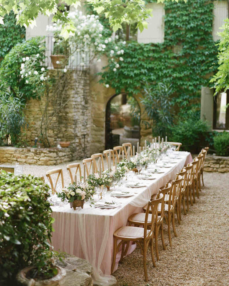 blush tablecloths and tulle overlays, blush flower and greenery centerpieces for these long tables