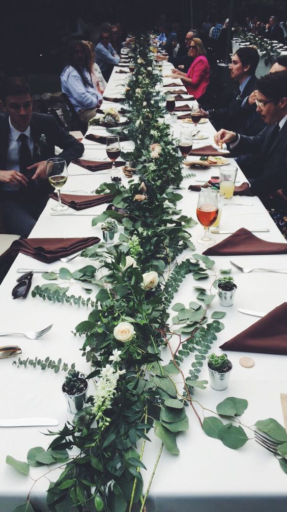 long tables plus lush greenery and white bloom centerpieces for a chic modern look