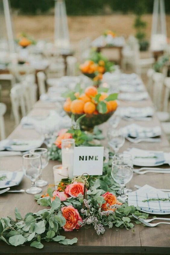 lush greenery and orange blooms plus peach centerpieces in bowls and simple table numbers