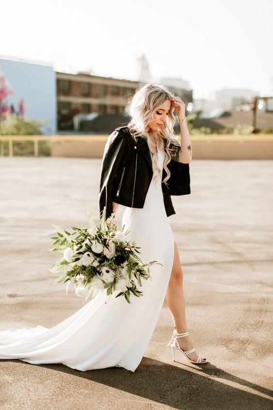 the bride rocking a white minimalist wedding dress, white strappy shoes and a black leather jacket