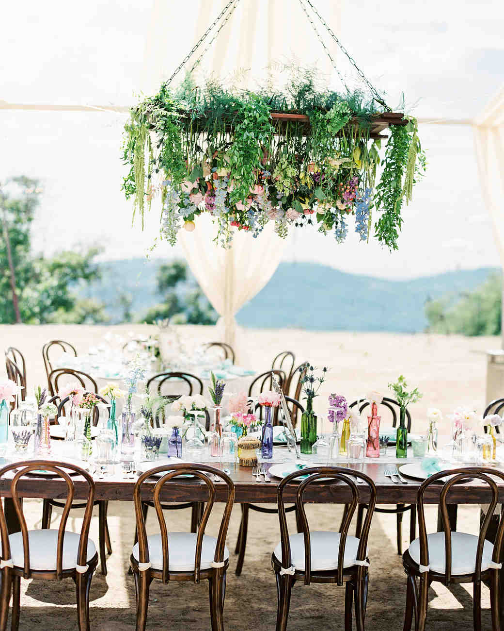 the colorful glass bottles on this dreamy tablescape were matched perfectly to the flowers hanging above