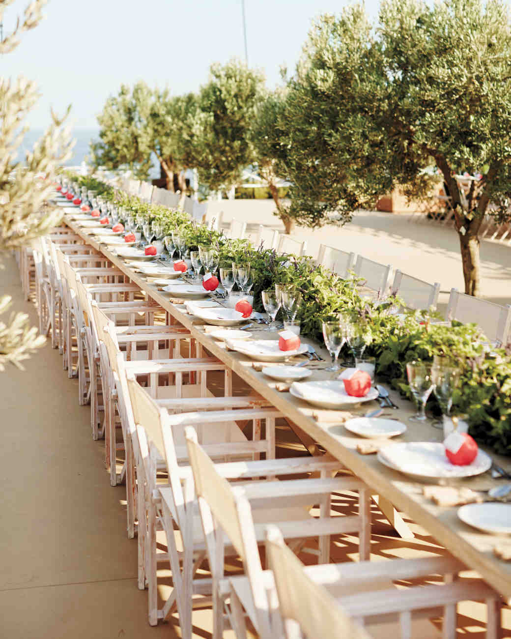 the cream colored tables and chairs at this reception offered a clean backdrop for length wise greenery