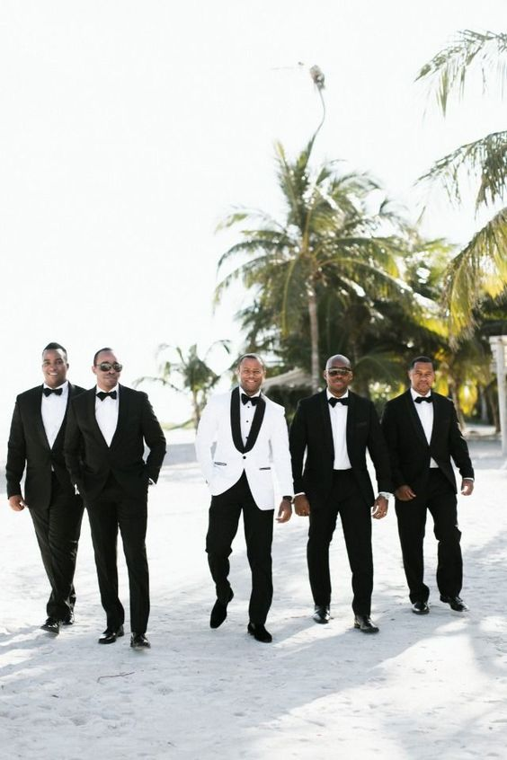 the groom in a white tux and the groomsmen wearing black tuxes for an elegant formal wedding