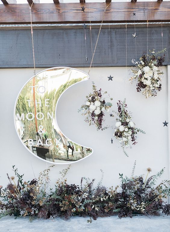 a beautiful wedding backdrop with a shiny silver moon, lush florals and dark and dried herbs and leaves