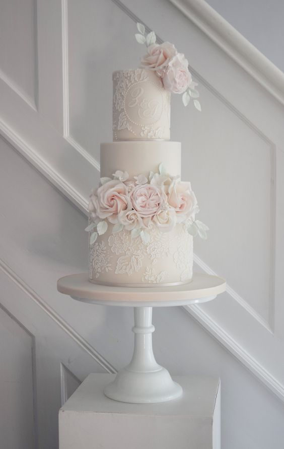 a blush wedding cake with white lace patterns, blush sugar blooms and white leaves of sugar is very tender and cute