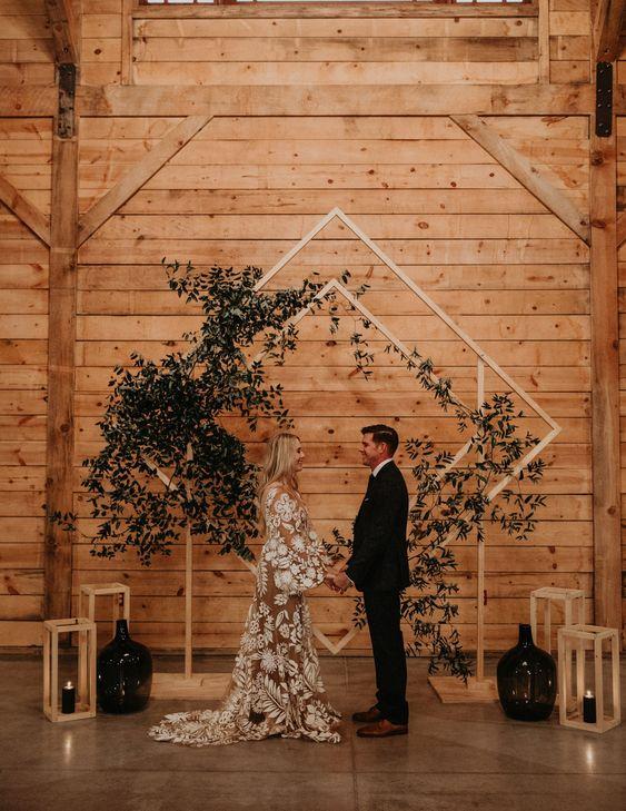 a boho wedding altar of a geometric base and lush greenery plus candles around it