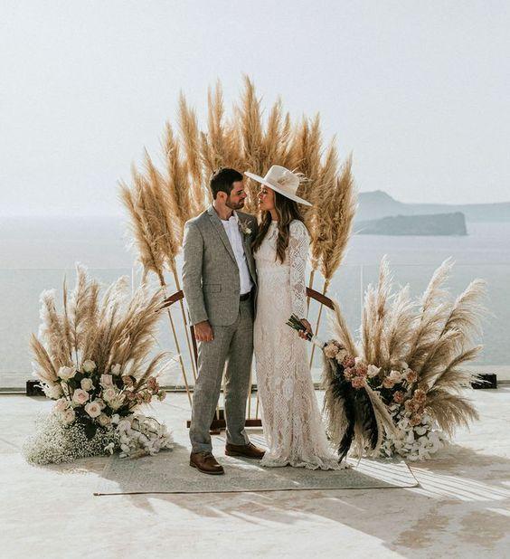 a boho wedding altar of pampas grass, pastel blooms and some foliage plus a sea view for a boho wedding