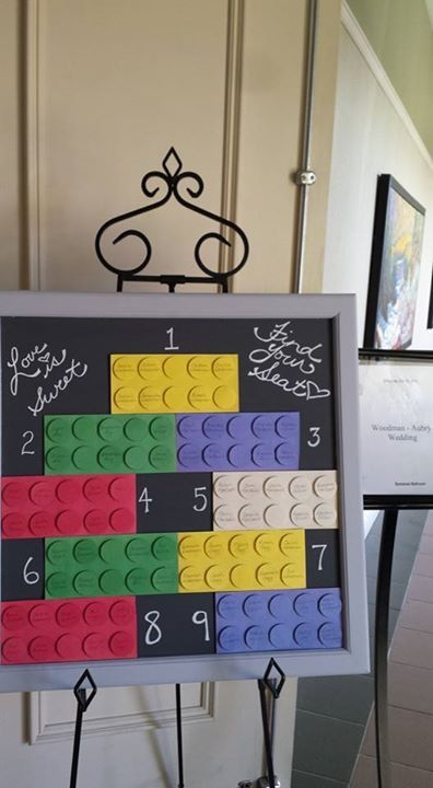 a bright Lego wedding seating chart with colorful Lego elements on the chalkboard