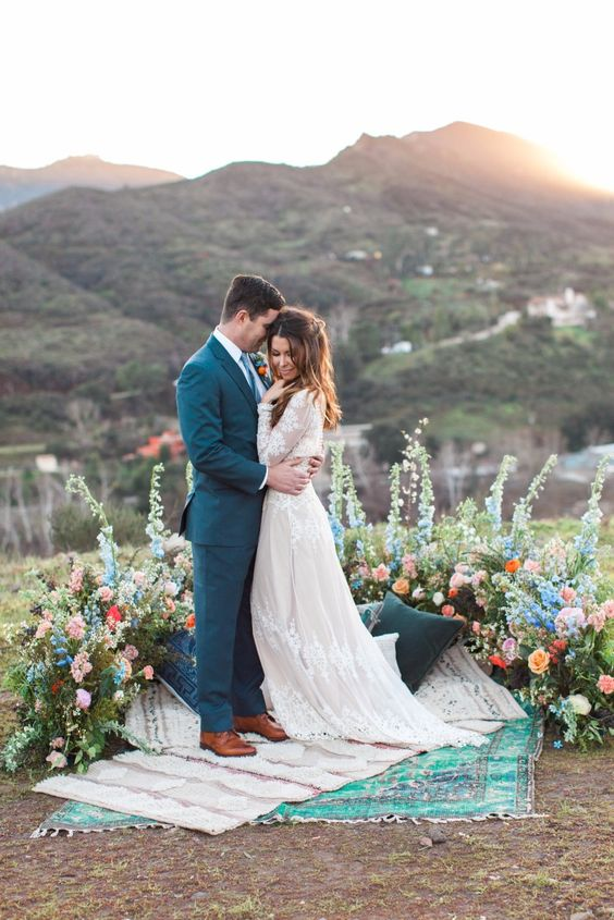 a bright boho wedding altar of colorful blooms with greenery and layered boho rugs is a cool piece