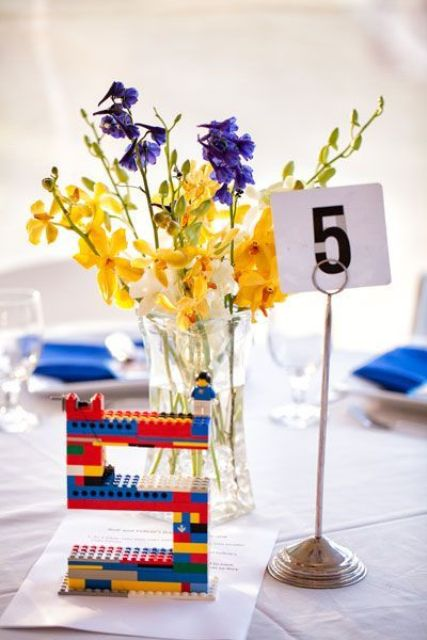 a bright wedding centerpiece of yellow and purple blooms, a colorful Lego table number for a playful wedding
