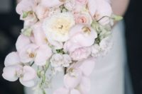 a cascading bouquet with blush orchids and white peonies looks luxurious, chic and romantic