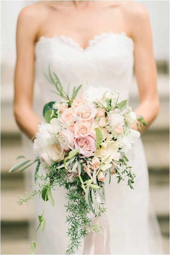 a cascading pastel wedding bouquet with blush and peachy blooms, greenery of various kinds