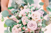 a chic blush and lilac wedding bouquet with various kinds of blooms and greenery